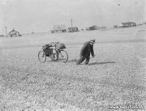 An old man pulling his tricycle along the shingle beach at Dungeness in Kent with some effort . 1935