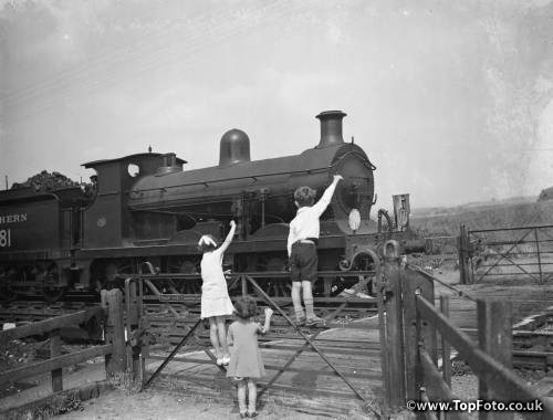 children waving to the train driver . 1936