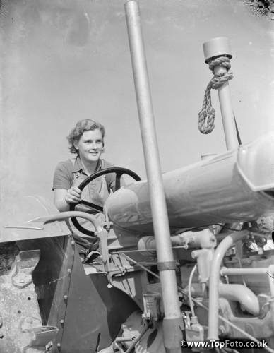 Women 's Land Army in training on the fields of Wye , Kent  . Here a Land Girl is getting practice on using a tractor . 1939
